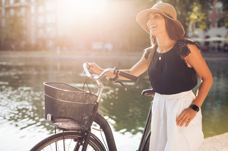 Portrait of beautiful young woman wearing a hat with a bicycle walking along a pond. Happy woman with a bike at the park looking away laughing on a summer day, with sun flare.