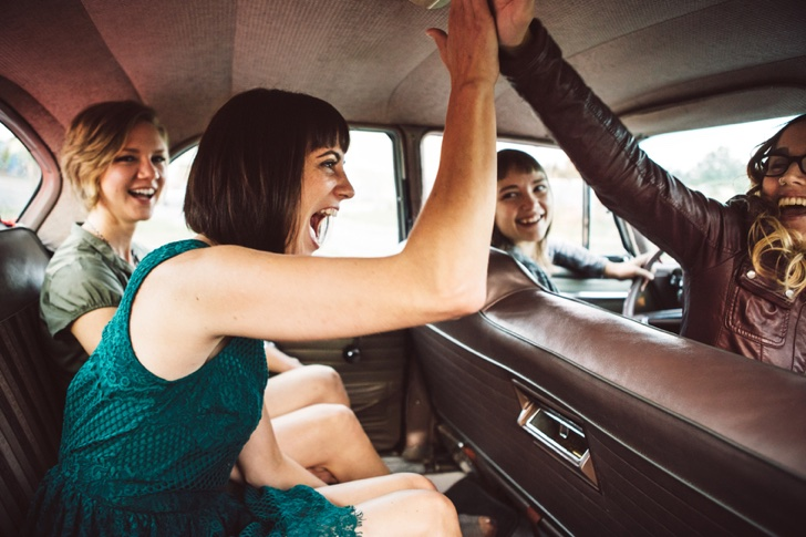 A group of young women laugh and have fun on a road trip adventure in a classic car, two of them giving each other a high five. Horizontal image.